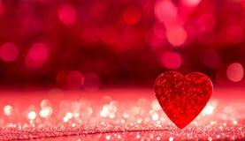 Valentinsgruß `s Tag Helles rotes Herz auf dem Glänzen des roten Hintergrundes mit bokeh Effekt stockbilder
