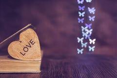 Valentinsgruß `s Tag Herzbuch bokeh von Schmetterlingen Hölzernes Herz mit der Wortliebe Lizenzfreie Stockfotos