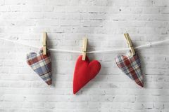 Valentinsgruß `s Tag Hintergrund der hellen Backsteinmauer Handgemachte Rot- und Textilherzen im Käfig werden auf einem Seil gewo lizenzfreie stockfotografie