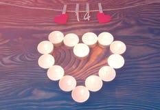 Valentinsgruß `s Tag Inneres der Kerzen Rote hölzerne Herzen mit Stiften und Zahlen von FEB 14 hängend am Seil auf dem Braun hölz stockfoto