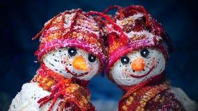 Valentinsgruß `s Tag Liebhaber von Schneemännern sind im Schnee und halten die Herzen des Gewebes stock video