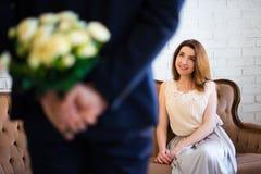 Valentinsgruß ` s Tag oder Jahrestagskonzept - bemannen Sie versteckende Blumen von Stockfoto