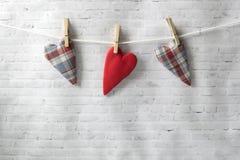 Valentinsgruß `s Tag Rastre Bild Handgemachte Textilherzen wiegen auf einem Seil, befestigt mit einer Wäscheklammer lizenzfreies stockfoto