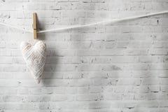 Valentinsgruß `s Tag Rastre Bild Handgemachtes Weinlesetextilherz, das an einem Seil, befestigt mit einer Wäscheklammer hängt stockfotografie