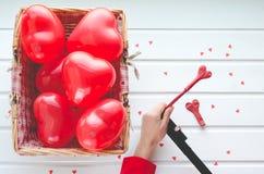 Valentinsgruß ` s Tag, steigt rote Herzen auf weißem hölzernem Hintergrund im Ballon auf, Stockbild