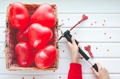 Valentinsgruß ` s Tag, steigt rote Herzen auf weißem hölzernem Hintergrund im Ballon auf, Stockfotografie