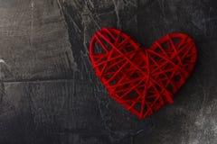 Valentinsgruß ` s Tagesdunkler Hintergrund mit einem roten Herzen Ansicht von oben Platz für Text Stockbilder