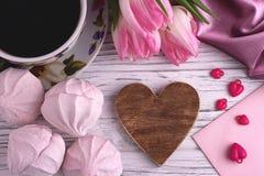 Valentinsgruß ` s Tageselegantes Stillleben mit Tulpe blüht Schale Herz-Formzeichens coffe Eibisches des roten auf weißem hölzern Stockfotos