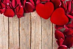 Valentinsgruß ` s Tageshintergrund, rote Herzen und Blumenblätter auf Tabelle, Funkelnhintergrund Lizenzfreie Stockbilder