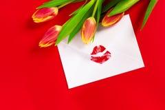 Valentinsgruß ` s Tageshintergrund Umschlag mit rotem Lippenstiftkuß und -tulpen auf Rot stockfotografie