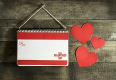 Valentinsgruß ` s Tageskarte mit Herzen eines Notizbuches und des Papiers Lizenzfreie Stockfotografie