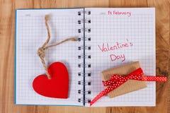 Valentinsgruß-Tag geschrieben in Notizbuch, in eingewickeltes Geschenk und in Herz, Dekoration für Valentinsgrüße Lizenzfreie Stockbilder