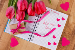 Valentinsgruß-Tag geschrieben in Notizbuch, in frische Tulpen, in eingewickeltes Geschenk und in Herzen, Dekoration für Valentins Lizenzfreies Stockfoto