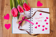 Valentinsgruß-Tag geschrieben in Notizbuch, in frische Tulpen, in eingewickeltes Geschenk und in Herzen, Dekoration für Valentins Stockfotografie