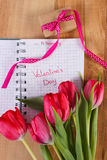 Valentinsgruß-Tag geschrieben in Notizbuch, in frische Tulpen und in eingewickeltes Geschenk, Dekoration für Valentinsgrüße Stockfotos