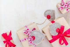 Valentinsgruß-Tagesgeschenke übergeben genähten Herzen altes Papier Stockfoto