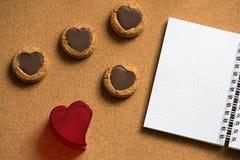 Valentinsgruß-Tageshintergrund mit Plätzchenherzen auf dem hölzernen Muster mit Notizbuch Stockbilder