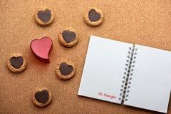 Valentinsgruß-Tageshintergrund mit Plätzchenherzen auf dem hölzernen Muster mit Notizbuch Stockbild