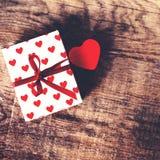 Valentinsgruß-Tageshintergrund mit rotem Herzen und anwesendes Geschenk flehen an an Stockfotos