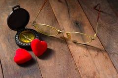 Valentinsgruß-Tageskompaß auf hölzernem Hintergrund mit Herzen und Glas Stockbild