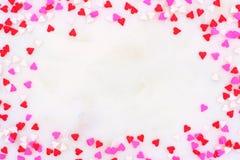 Valentinsgruß-Tagessüßigkeitsherz besprüht Rahmen über einem weißen strukturierten Hintergrund stockfotos
