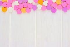 Valentinsgruß-Tagessüßigkeitsherzen übersteigen Grenze über weißem Holz Stockbilder