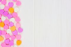 Valentinsgruß-Tagessüßigkeitsherzen versehen Grenze über weißem Holz mit Seiten stockfoto