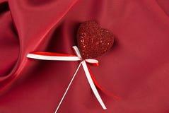 Valentinsgrußgeschenk auf roter Seide Stockbild