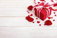 Valentinsgrußgeschenk mit den rosafarbenen Blumenblättern, hölzerner Kopienraum stockfoto