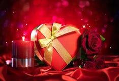 Valentinsgrußgeschenkbox und rosafarbene Blume auf roter Seide Stockfoto