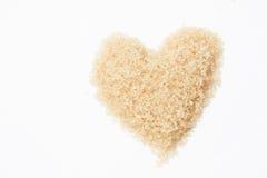 Valentinsgrußherz des süßen braunen Zuckers auf weißem Hintergrund Lizenzfreie Stockfotos