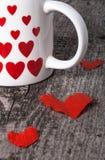 Valentinsgrußherzen und Tasse Tee auf dem alten Holztisch Lizenzfreie Stockfotos