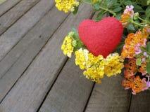 Valentinsgrußhintergrund, rotes Herz und bunte fowers auf hölzernem Stockbilder
