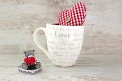Valentinsgrußminiaturteddybär und rotes Herz auf hölzernem backgroun Stockbilder