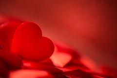 Valentinsgrußsatinherz auf rotem Hintergrund, Symbol der romantischen Liebe Stockbild