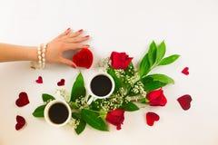 Valentinsgrußstillleben mit Perlenring in der Mannhand, in den roten Rosen und in der Frauenhand mit Kaffee Stockbilder