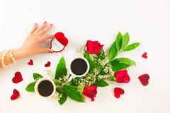 Valentinsgrußstillleben mit Perlenring in der Mannhand, in den roten Rosen und in der Frauenhand mit Kaffee Stockfoto