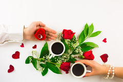 Valentinsgrußstillleben mit Perlenring in der Mannhand, in den roten Rosen und in der Frauenhand mit Kaffee Lizenzfreie Stockfotografie