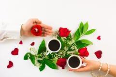 Valentinsgrußstillleben mit Perlenring in der Mannhand, in den roten Rosen und in der Frauenhand mit Kaffee Lizenzfreies Stockfoto