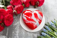 Valentinsgrußtages- oder -geburtstagsgrußkarte Kuchen in Form eines roten Herzens Rote Rosen und Nachtisch auf Weinleseholztisch Lizenzfreie Stockfotografie