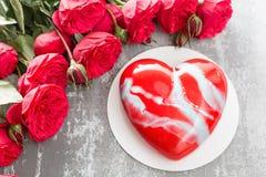 Valentinsgrußtages- oder -geburtstagsgrußkarte Kuchen in Form eines roten Herzens Rote Rosen und Nachtisch auf Weinleseholztisch Lizenzfreie Stockfotos