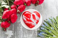 Valentinsgrußtages- oder -geburtstagsgrußkarte Kuchen in Form eines roten Herzens Rote Rosen und Nachtisch auf Weinleseholztisch Stockfotografie