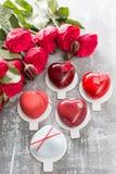 Valentinsgrußtages- oder -geburtstagsgrußkarte Verlosen Sie Nachtische in Form eines roten Herzens Rote Rosen und Nachtisch auf W Stockbilder