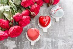 Valentinsgrußtages- oder -geburtstagsgrußkarte Verlosen Sie Nachtische in Form eines roten Herzens Rote Rosen und Nachtisch auf W Stockfotografie
