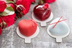 Valentinsgrußtages- oder -geburtstagsgrußkarte Verlosen Sie Nachtische in Form eines roten Herzens Rote Rosen und Nachtisch auf W Stockfotos