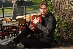 Valentinsgrußtages- und -feiertagsfeierkonzept Mann mit rotem Herzballon Kerl, der auf Bank unter Baum sitzt Stockbild