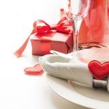 Valentinsgrußtagesabendessen mit Tabellengedeck mit rotem Geschenk, eine Flasche Champagner, Herzverzierungen mit Tafelsilber auf lizenzfreie stockfotos
