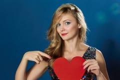 Valentinsgrußtagesfrau, die rotes Herz mit Liebe zeigt Lizenzfreie Stockfotos