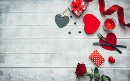 Valentinsgrußtagesgedeck mit Gabel, Messer, roten Herzen, Band und Rosen lizenzfreie stockfotos