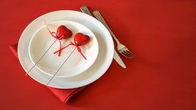 Valentinsgrußtagesgedeck mit zwei Herzen gabeln und Messertischdecke auf rotem Hintergrund Romantisches Gedeck für Valentinsgrüße stockfoto